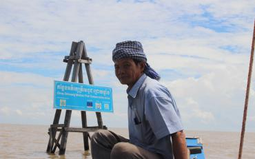 Mr Om Chhim, CFiC member, sits in front of one of six demarcation towers and the FCA signboard in Kampong Phluk CFi